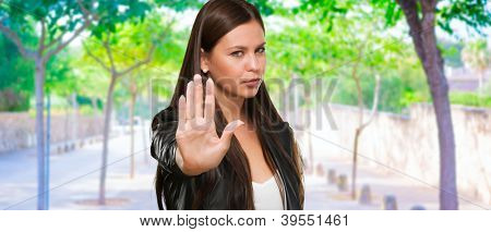 Young Woman Showing Stop Hand Gesture at a park