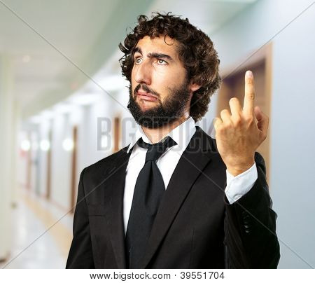 Portrait Of An Unhappy Businessman Pointing Up, indoor