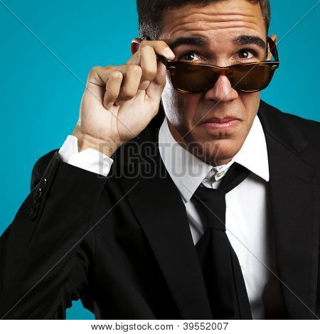 portrait of business man taking off the sunglasses against a blue background