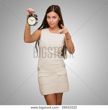 Woman Holding Alarm Clock and pointing against a grey background