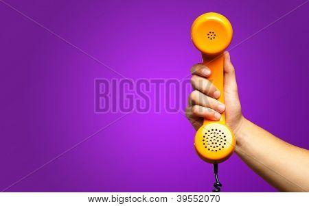 Close Up de mão segurando telefone contra um fundo roxo