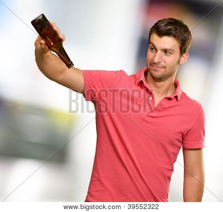 Portrait Of Young Man Holding Empty Bottle, Outdoor