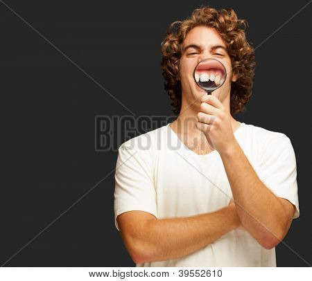 Man Examining His Teeth With Magnifier On Black Background