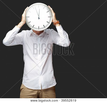 Young Man Holding Big Clock Covering His Face On Black Background