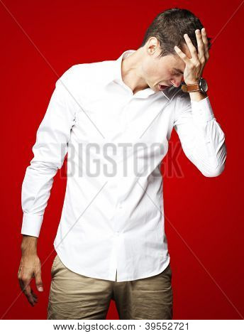 Angry young man doing frustration gesture over red background