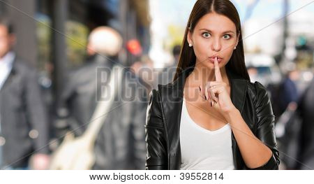 Woman Making A Keep It Quiet Gesture against a street background