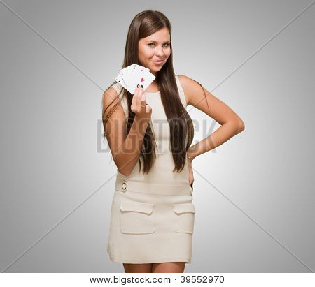 Young Woman Holding Playing Cards against a grey background