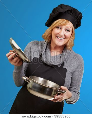 Middle aged cook woman holding a sauce pan over blue background