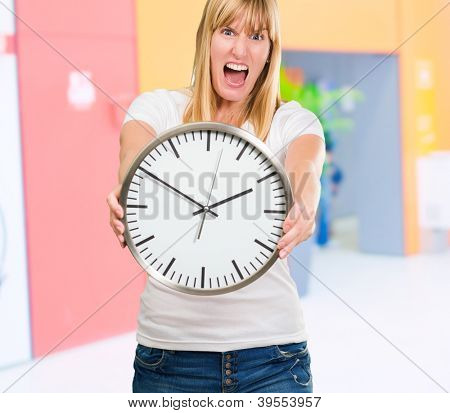 Portrait Of A Angry Woman Holding Clock against an abstract background