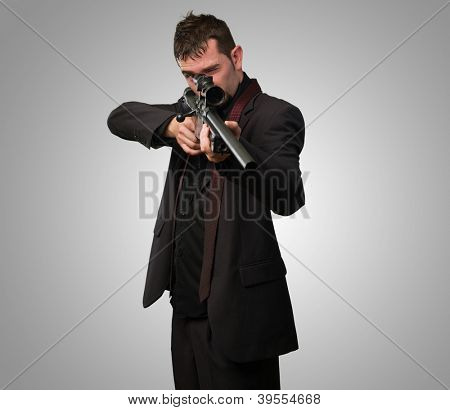 Man in suit pointing with a rifle against a grey background