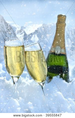 Two glasses of champagne in snow with mountain in background
