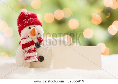 Cute Snowman with Scarf and Hat Next To Blank White Card Over Abstract Background