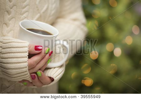 Woman in Sweater with Seasonal Red and Green Nail Polish Holding a Warm Cup of Coffee.