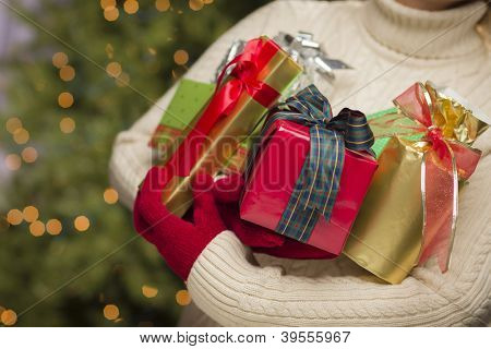 Woman Wearing A Sweater and Seasonal Red Mittens Against an Abstract Green and Golden Background Holding Beautifully Wrapped Christmas Gifts.