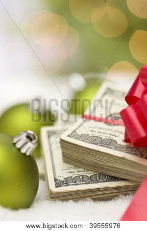 Stack of One Hundred Dollar Bills with Red Bow Near Green Christmas Ornaments on Snow Flakes.