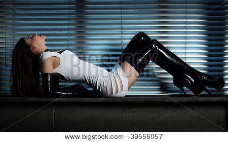 Young slim goth woman. On window background.