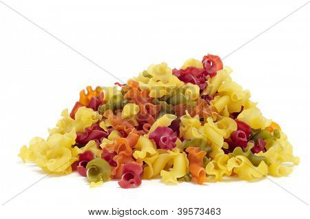 a pile of uncooked vegetables gigli pasta on a white background