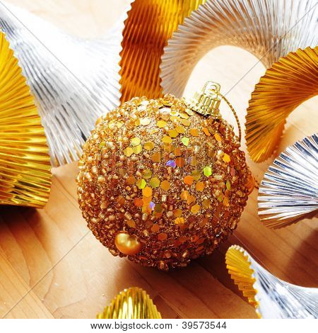 a golden christmas ball and golden and silver garland on a wooden surface