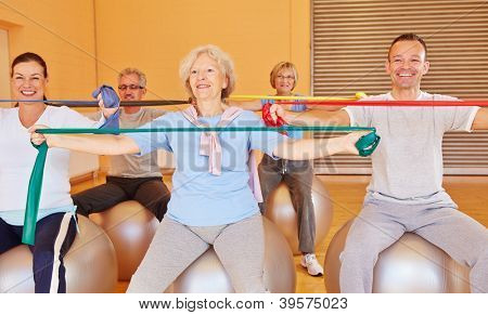 Group of happy senior people doing back training with exercise band in gym