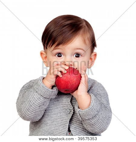 Adorable baby girl eating a red apple isolated on white background