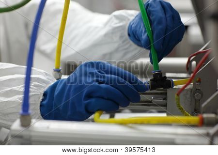 hands in blue gloves fixing problem at industrial process line  - close up