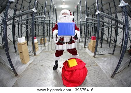 Santa Claus preparing for Christmas,showing gift  in empty storehouse, fish-eye photo