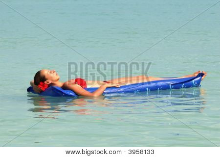 Woman Swimming On An Air Mattress