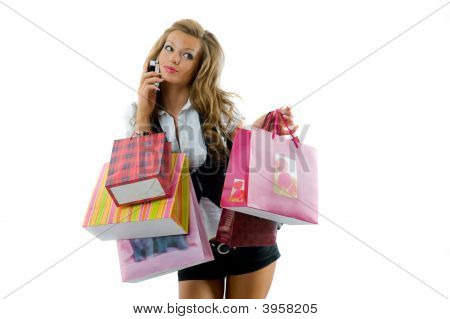 Happy Young Woman On A Shopping Spree. Talking By Phone