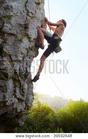 Young man climbing vertical natural rocky wall with clear sky on the background