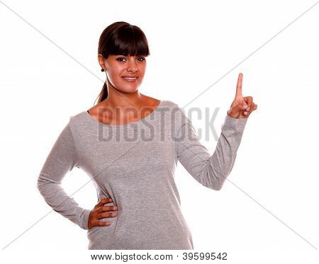 Stylish Young Female Looking At You Pointing Up