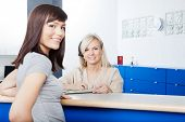stock photo of receptionist  - Portrait of young woman with receptionist filling form at desk in dentist - JPG