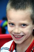 image of ooze  - Little boy smiles sheepishly for the camera - JPG