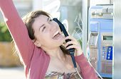 stock photo of long distance relationship  - A happy woman talking at a landline phone - JPG