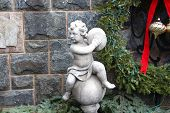 Cherub with cymbals and holiday greenery