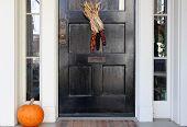Постер, плакат: черная дверь с кукуруза и тыквы