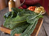 stock photo of cruciferous  - Lacinato kale on a wooden cutting board with other vegetables in the background - JPG