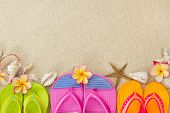 stock photo of frangipani  - Flip Flops in the sand with shells and frangipani flowers - JPG