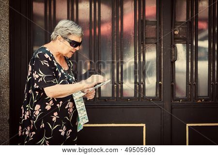 Senior Woman Selling Lottery Coupons In The Street