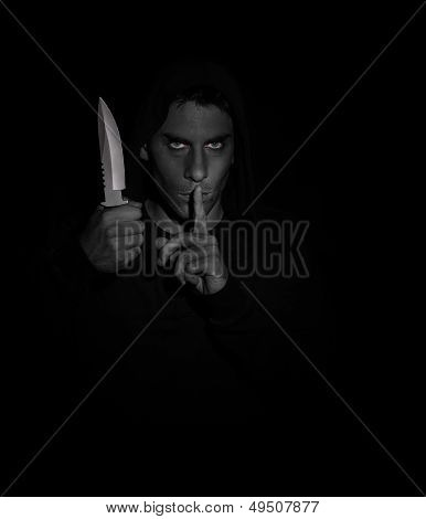 Evil Man Gesturing Silence While Holding A Knife