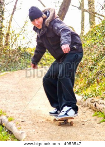 Excited Young Guy Skateboarding Down A Hill