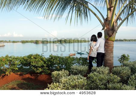 Portrait Of Happy Couple Under Coconut Tree