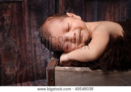 Smiling Newborn Baby Boy Sleeping In A Rustic Crate