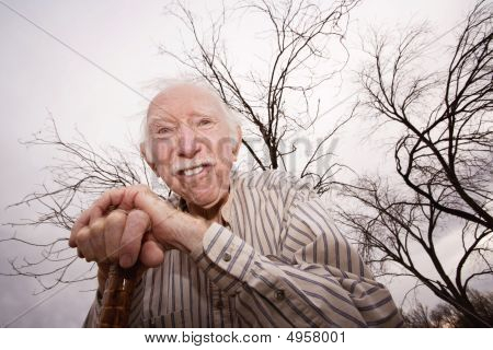 Old Man In Front Of Bare Trees