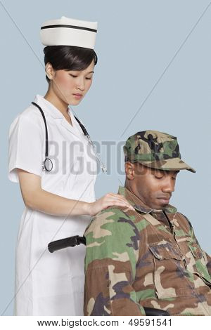 Female nurse comforting disabled US Marine Corps soldier in wheelchair over light blue background