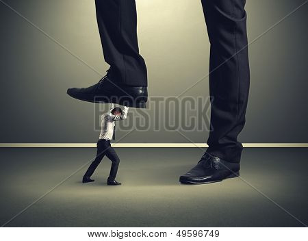 small businessman under big leg his boss
