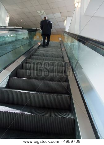 Man In Suit Riding Escalator