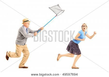 Full length portrait of a scared young female trying to runaway from mature man with butterfly net isolated on white background