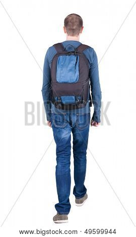 back view walking ma  with backpack. brunette guy in motion. backside view person.  Rear view people collection. Isolated over white background. young man goes to side of rolling travel bag on wheels