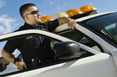 stock photo of policeman  - Police Officer Leaning on Patrol Car - JPG