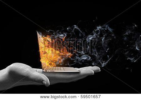 Human hand holding burning laptop on palm
